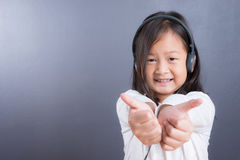 Portrait d'écouteur asiatique d'utilisation de petite fille et de téléphone intelligent Image libre de droits