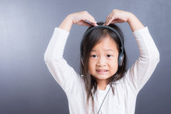 Portrait d'écouteur asiatique d'utilisation de petite fille et de téléphone intelligent Photographie stock libre de droits