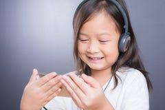 Portrait d'écouteur asiatique d'utilisation de petite fille et de téléphone intelligent Photos stock