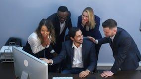 Portrait d'équipe choquée d'affaires par la table regardant l'ordinateur portable dans le bureau Image stock