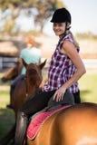 Portrait d'équitation de femme avec l'ami s'asseyant sur le cheval à l'arrière-plan Images stock