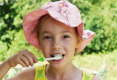 Portrait d'été des dents de brossage de fille adorable Photo stock