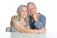 Portrait d'étreindre les couples supérieurs se reposant à la table Photographie stock