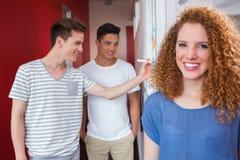 Portrait d'étudiant de sourire avec des amis derrière elle Image stock