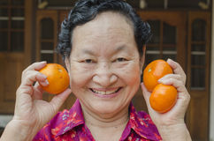 Portrait d'aîné asiatique tenant l'orange Image libre de droits