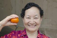 Portrait d'aîné asiatique tenant l'orange Photographie stock libre de droits