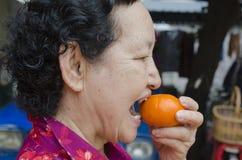 Portrait d'aîné asiatique tenant l'orange Images stock