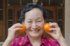 Portrait d'aîné asiatique tenant l'orange Photos stock