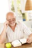 Portrait d'aîné riant avec le livre Photos stock