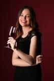 Portrait d'ado dans la robe noire avec du vin Fin vers le haut Fond rouge foncé Photos libres de droits