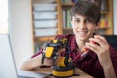 Portrait d'adolescent construisant le bras robotique à l'école image libre de droits