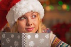 Portrait d'adolescente dans le chapeau de Santa avec le journal intime dans la cuisine Photos stock