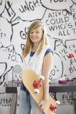 Portrait d'adolescente heureuse tenant la planche à roulettes à la maison Image libre de droits