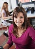 Portrait d'adolescente souriant dans la classe d'ordinateur Image stock