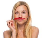 Portrait d'adolescente tenant le poivre de piment rouge comme mustage Images libres de droits