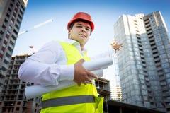Portrait d'agent de maîtrise dans le casque montrant le chantier sous le constr Photos libres de droits