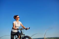 Portrait d'ajustement sain et de femme mûre sportive, sûre et réussie faisant un cycle sur le vélo de montagne Photos libres de droits
