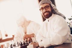 Portrait d'Arabe avec des verres jouant aux échecs photo stock
