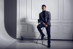 Portrait d'attrayant, d'une manière élégante hommes dans le costume gris et verres, posant dans le studio sur le fond blanc images stock