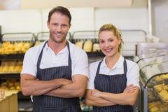 Portrait d'boulangers de sourire avec des bras croisés Photo stock