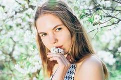 Portrait d'embrasser une jeune fille de fleur dans le jardin de cerise Photo libre de droits