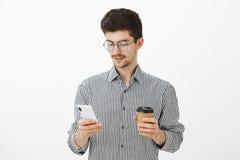 Portrait d'employé européen ordinaire focalisé dans les verres ronds et la chemise rayée, tenant le smartphone et la tasse de caf Photos stock