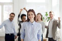 Portrait d'employé féminin réussi avec les collègues enthousiastes a photo libre de droits