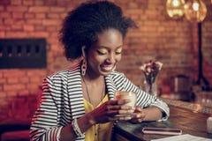 Portrait d'enchanter la tasse de participation femelle afro-américaine de café en verre images libres de droits