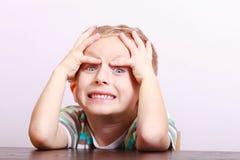 Portrait d'enfant blond émotif fâché étonné d'enfant de garçon à la table Photographie stock libre de droits