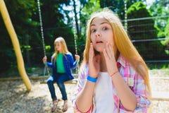 Portrait d'enfant d'offense au parc Sur le fond l'autre fille montant une oscillation Images stock