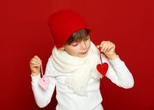 Portrait d'enfant de fille avec des coeurs sur le rouge, concept de vacances d'hiver Photo libre de droits