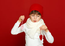 Portrait d'enfant de fille avec des coeurs sur le rouge, concept de vacances d'hiver Photo stock