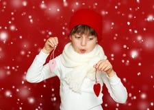 Portrait d'enfant de fille avec des coeurs sur le rouge, concept de vacances d'hiver Image stock
