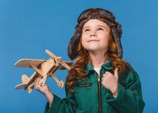 portrait d'enfant de sourire dans le costume pilote avec le jouet plat en bois Photographie stock