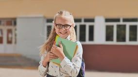 Portrait d'enfant de sourire de fille d'école avec le sac à dos et les livres banque de vidéos