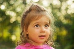 portrait d'enfant regardant avec l'intérêt pour le fond brillant Photographie stock libre de droits