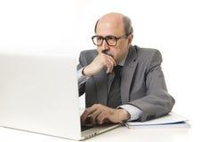 Portrait d'entreprise 60s chauve sérieux et homme autoritaire d'affaires pensant et travaillant au bureau d'ordinateur portable d Photo libre de droits