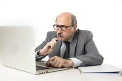 Portrait d'entreprise 60s chauve sérieux et homme autoritaire d'affaires pensant et travaillant au bureau d'ordinateur portable d Photo stock