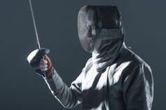 Portrait d'escrimeur professionnel dans le masque de clôture avec la rapière Photos libres de droits