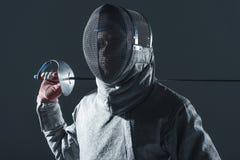 Portrait d'escrimeur professionnel dans le masque de clôture avec la rapière Image libre de droits