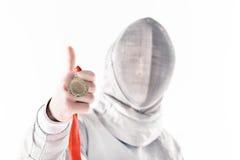 Portrait d'escrimeur professionnel dans le masque de clôture tenant la médaille avec le pouce  Images libres de droits