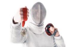 Portrait d'escrimeur professionnel dans le masque de clôture tenant la médaille et la rapière Photo libre de droits