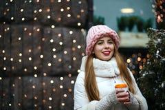 Portrait d'hiver de la jeune dame de belle brune utilisant l'équipement à la mode chaud, café chaud potable à la rue L'espace pou photographie stock