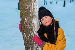 Portrait d'hiver d'une gentille petite fille près d'un arbre l'enfant utilise un chapeau d'hiver photos libres de droits