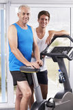 Portrait d'homme âgé par milieu avec l'entraîneur personnel In Gym image stock