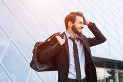 Portrait d'homme d'affaires barbu de sourire de hippie dans le costume avec le sac sur le fond de fenêtres de gratte-ciel photos stock