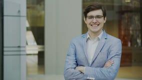 Portrait d'homme d'affaires de sourire réussi en verres regardant dans l'appareil-photo dans le bureau moderne