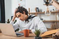portrait d'homme d'affaires fatigué se reposant sur le lieu de travail avec l'ordinateur portable et la tasse de café Images stock