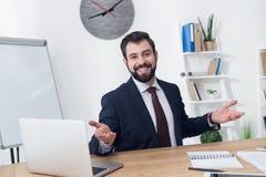 portrait d'homme d'affaires gai sur le lieu de travail avec l'ordinateur portable Photo stock
