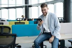 Portrait d'homme d'affaires réussi dans des message textuels de lecture d'immeuble de bureaux de smartphone photos stock